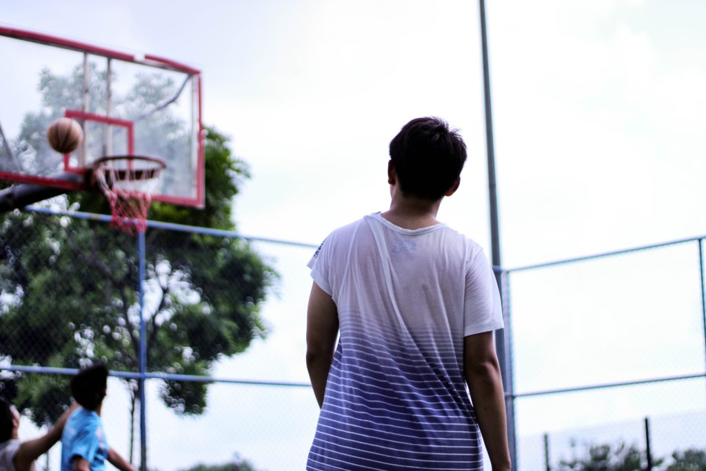 man-standing-near-red-basketball-hoop-system-1410166